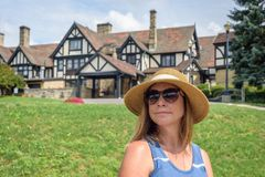 Woman in sunhat sitting in front of tudor style mansion Royalty Free Stock Photo