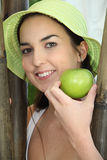 Woman with sunhat. Smiling woman with sunhat and apple Stock Photography