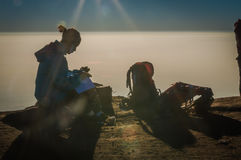Woman in sunlight. Central Java, Indonesia - May 2015: Photo of woman sitting on stone and writing in sunlight during sunrise near Yogya in central Java province Stock Photography