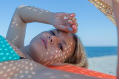 Woman with sunlight through holes on her face. Portrait of young woman with sunlight through holes on her face. Attractive young woman lying on back, holding Royalty Free Stock Photos