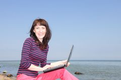 A woman on a sunny beach working on a laptop Royalty Free Stock Photo