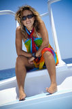 Woman on sunny vacation. Happy woman relaxing on boat while on a sunny, tropical vacation Royalty Free Stock Image