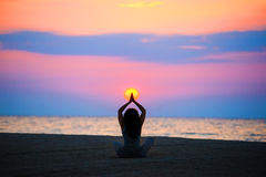 Woman at sunrise doing yoga exercise on the sea shore Royalty Free Stock Photos