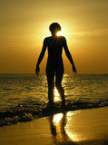Woman at sunrise with sun in head. Beach Stock Photography