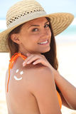 Woman with sunscreen. On the beach wearing a hat Royalty Free Stock Photo