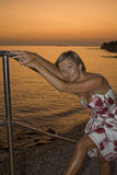 Woman at sunset. Young woman wrapped in tank top dress at the sunset beach Stock Image