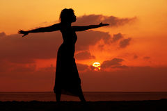 Woman at sunset. Dramatic image of a woman by the ocean at sunset Royalty Free Stock Photography