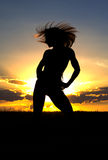 Woman at sunset. Silhouetted woman with long blowing hair exercising with golden sunset background Royalty Free Stock Photos