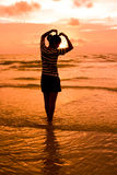 Woman at sunset. Silhouetted woman with golden sunset background Stock Photo