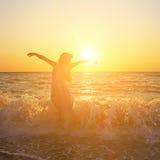 Woman at sunset. Beautiful romantic woman at the seaside at sunset Stock Photo