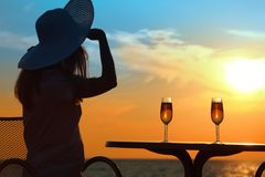 Woman on sunset behind table with glasses Stock Images