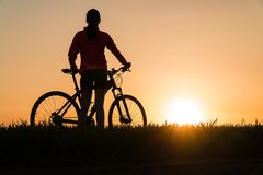 Woman at sunset from sunset Bike bike. woman practicing sports stock photo
