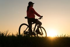 Woman at sunset from sunset Bike bike. woman practicing sports royalty free stock photography