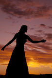 Woman in sunset reaching Royalty Free Stock Photo