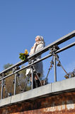 Woman sunshines enjoys sunlight on bridge. And keeps maple bouquet in hand Royalty Free Stock Photography