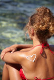 Woman with suntan lotion at the beach Stock Images