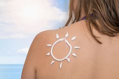 Woman with suntan lotion on her shoulder in sun shape. Sunbathing concept stock photo