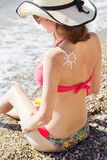 Woman with suntan spf cream on her back Royalty Free Stock Photos