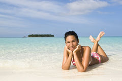 Woman suntanning on white sand beach Royalty Free Stock Image