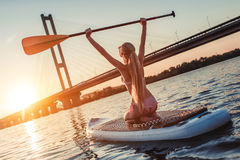 Woman on SUP board. Woman on stand up paddle board. Having fun on SUP board during sunset. Active lifestyle Stock Photo