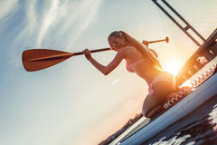 Woman on SUP board. Woman on stand up paddle board. Having fun on SUP board during sunset. Active lifestyle Stock Photography
