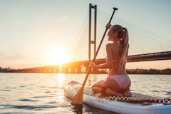Woman on SUP board. Woman on stand up paddle board. Having fun on SUP board during sunset. Active lifestyle Royalty Free Stock Photo