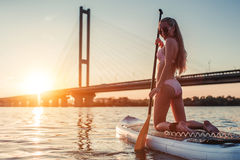 Woman on SUP board. Woman on stand up paddle board. Having fun on SUP board during sunset. Active lifestyle Royalty Free Stock Images