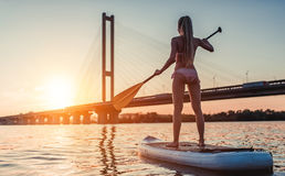 Woman on SUP board. Woman on stand up paddle board. Having fun on SUP board during sunset. Active lifestyle Stock Images