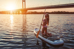 Woman on SUP board. Woman on stand up paddle board. Having fun on SUP board during sunset. Active lifestyle Stock Image