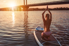 Woman on SUP board. Woman on stand up paddle board. Having fun on SUP board during sunset. Active lifestyle. Yoga practicing Royalty Free Stock Photos