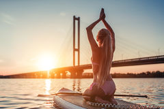 Woman on SUP board. Woman on stand up paddle board. Having fun on SUP board during sunset. Active lifestyle. Yoga practicing Stock Images