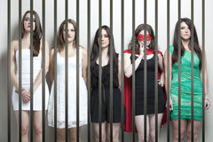 Woman in superhero costume with female friends standing behinds prison bars Stock Photography