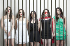 Woman in superhero costume with female friends standing behinds prison bars Royalty Free Stock Photos