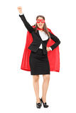 Woman in superhero costume with raised fist. Full length portrait of a woman in superhero costume with raised fist isolated on white background Royalty Free Stock Images