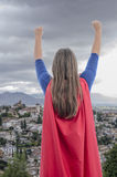 woman superhero with red cape and arms up, city background. Royalty Free Stock Photo