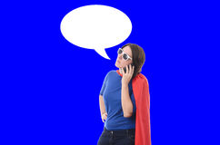 Woman superhero with red cape, blue background. Royalty Free Stock Images