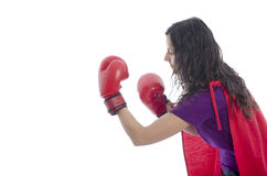 Woman superhero with red cape and red gloves boxing. Royalty Free Stock Image