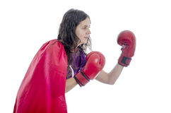 Woman superhero with red cape and red gloves boxing. Stock Photo