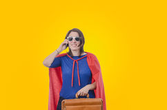 Woman superhero with red cape talking on the phone, orange. Royalty Free Stock Photo