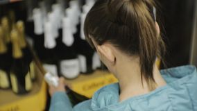 Woman in supermarket. Back view of young caucasian woman in blue jacket reading the label on the dark bottle choosing stock video