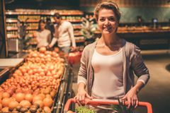 Woman at the supermarket. Beautiful women is looking at camera and smiling while doing shopping in supermarket Royalty Free Stock Image