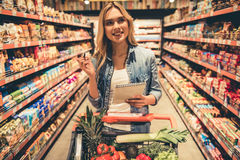 Woman at the supermarket. Beautiful young woman is holding a list of goods and smiling while doing shopping at the supermarket Royalty Free Stock Image
