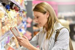 Woman in supermarket checking shopping list. On smartphone Stock Images