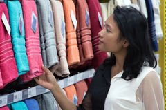 Woman in a supermarket chooses towel. Portrait of young woman in a supermarket. Asian woman chooses towel from the shelves at mall Royalty Free Stock Images
