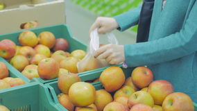 Woman in the supermarket coming up to the fruit counter. She choosing and putting apples in plastic bag stock video footage