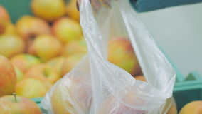 Woman in the supermarket coming up to the fruit counter. She choosing and putting apples in plastic bag stock footage