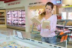 Woman in supermarket comparing two packs food Stock Images