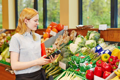 Woman in supermarket with data registration terminal. Young woman in supermarket with mobile data registration terminal Royalty Free Stock Photography
