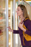 Woman in supermarket freezer section. Woman in a supermarket standing in front of the freezer looking for her favorite frozen food Stock Photos