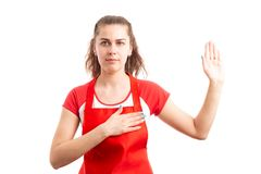 Woman supermarket or hypermarket worker making solemn vow. Young woman supermarket or hypermarket worker making solemn vow as serious employee concept isolated Stock Photo